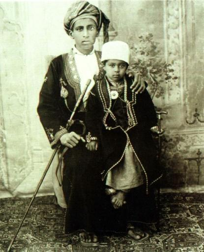 Qaboos is seen as a child sitting on his father's lap