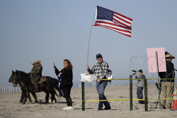 <p>A man holds a flag near the border Wednesday, Nov. 14, 2018, seen from Tijuana, Mexico. Migrants in a caravan of Central Americans scrambled to reach the U.S. border, catching rides on buses and trucks for hundreds of miles in the last leg of their journey Wednesday as the first sizable groups began arriving in the border city of Tijuana. (Photo: Gregory Bull/AP) </p>