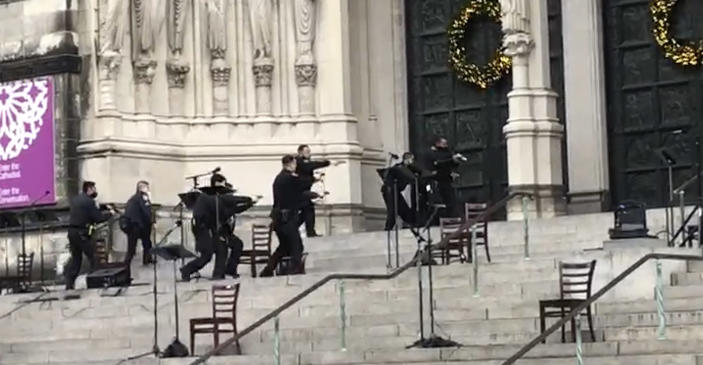 New York police officers move in on the scene of a shooting at the Cathedral Church of St. John the Divine, Sunday, Dec. 13, 2020, in New York. A man was shot by police after shots rang out at the end of a Christmas choral concert on the steps of the Manhattan cathedral Sunday afternoon. It's unclear if the gunman was killed or if any others were injured. The shooting happened just before 4 p.m. at the church which is the mother church of the Episcopal Diocese of New York and seat of its bishop. (AP Photo/Ted Shaffrey)