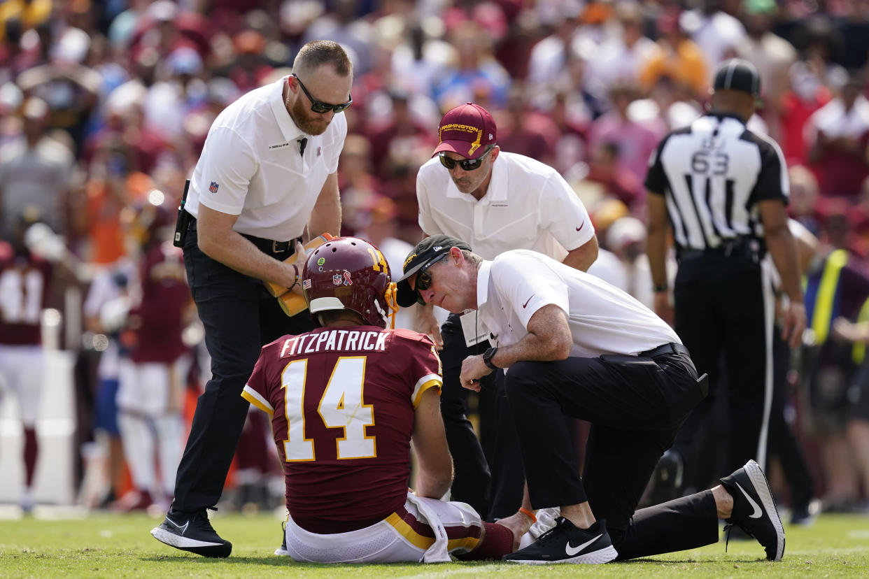 Members of the Washington Football Team staff check on condition of quarterback Ryan Fitzpatrick (14) after he was injured on a hit by Los Angeles Chargers linebacker Uchenna Nwosu during the first half of an NFL football game, Sunday, Sept. 12, 2021, in Landover, Md. (AP Photo/Alex Brandon)