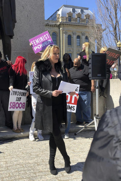 """Adult film star Stormy Daniels reads a statement, protesting the Illinois surcharge on live adult entertainment centers, beneath the statue of Abraham Lincoln at the state Capitol, Friday, March 22, 2019 in Springfield, Ill. The actress famous for her alleged affair with Donald Trump before he became president read a two-minute statement before she was whisked off to a local strip club to sign copies of her book. Daniels, whose real name is Stephanie Clifford, says the tax unfairly ties nude dancing to violence against women and that it """"takes money out of the g-strings of hardworking young dancers."""" (AP Photo/John O'Connor)"""