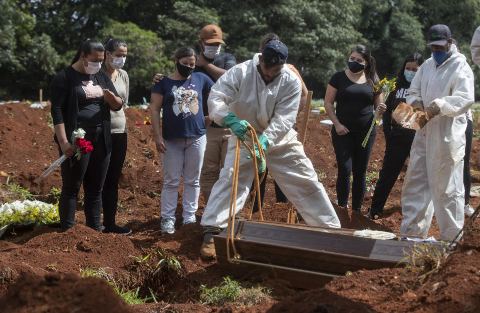 People attend the burial of a relative who died from complications related to COVID-19 at the Vila Formosa cemetery in Sao Paulo, Brazil, Wednesday, April 7, 2021. (AP Photo/Andre Penner)