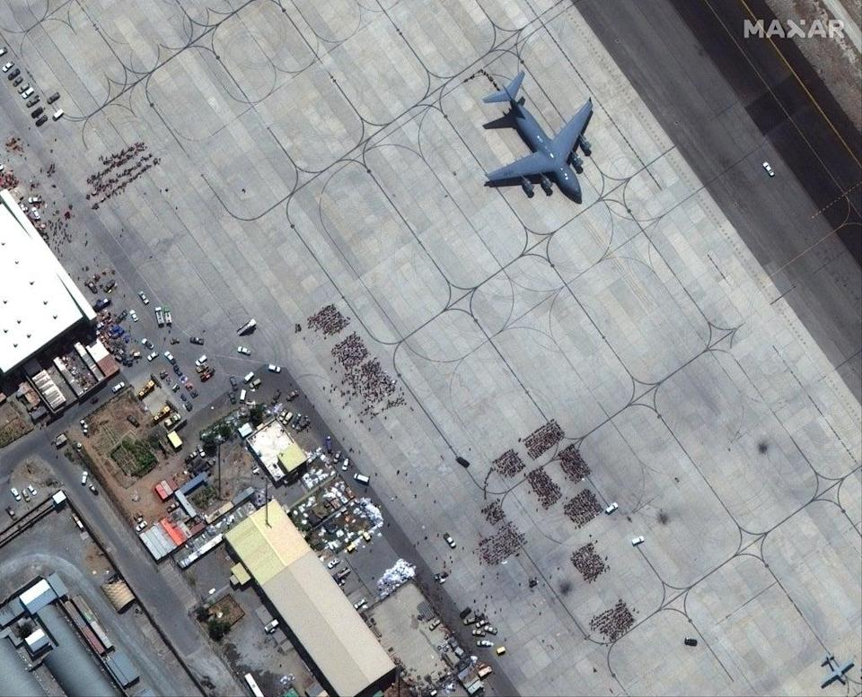 A satellite image shows groups of people waiting on the tarmac at Kabul Airport in Kabul, Afghanistan, 23 August 2021 (EPA-EFE)
