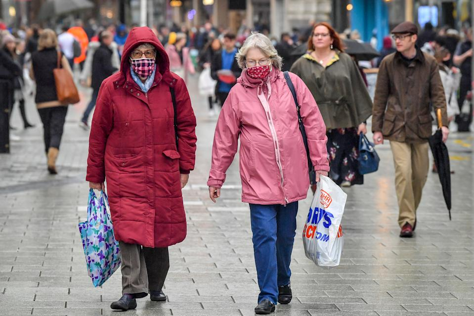 "Shoppers wearing face masks carry bags in the centre of Cardiff where shops are open and people are out in numbers taking advantage of buying nonessential items in the run-up to Christmas. Restrictions across Wales have been relaxed following a two-week ""firebreak"" lockdown."