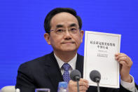 Xu Lin, Vice head of the Publicity Department of Communist Party shows a copy of the white paper on fighting COVID-19 China in action during a press conference at the State Council Information Office in Beijing, Sunday, June 7, 2020. Senior Chinese health officials defended their country's response to the new coronavirus pandemic, saying they provided information in a timely and transparent manner. (AP Photo/Andy Wong)
