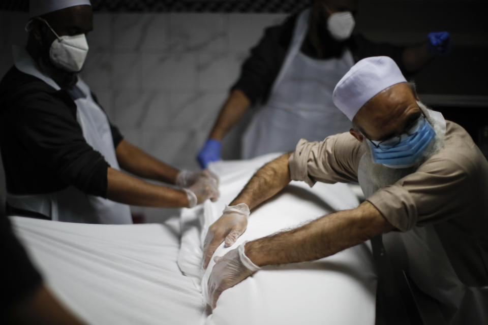 The body of Mohammad Altaf, who died at 48 of COVID-19, is ritually washed and wrapped before being given funeral prayers at Al-Rayaan Muslim Funeral Services, Sunday, May 17, 2020, in the Brooklyn borough of New York. (AP Photo/John Minchillo)