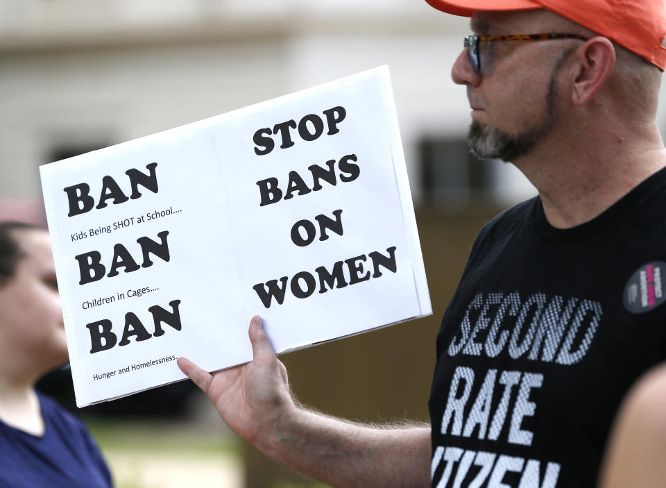 FILE - In this May 21, 2019, file photo, an abortion rights advocate hoists a sign at the Capitol in Jackson, Miss., as they rally to voice their opposition to state legislatures passing abortion bans. The Supreme Court has agreed to hear a potentially ground-breaking abortion case, and the news is energizing activists on both sides of the contentious issue. They're already girding to make abortion access a high-profile issue in next year's midterm elections. (AP Photo/Rogelio V. Solis, File)