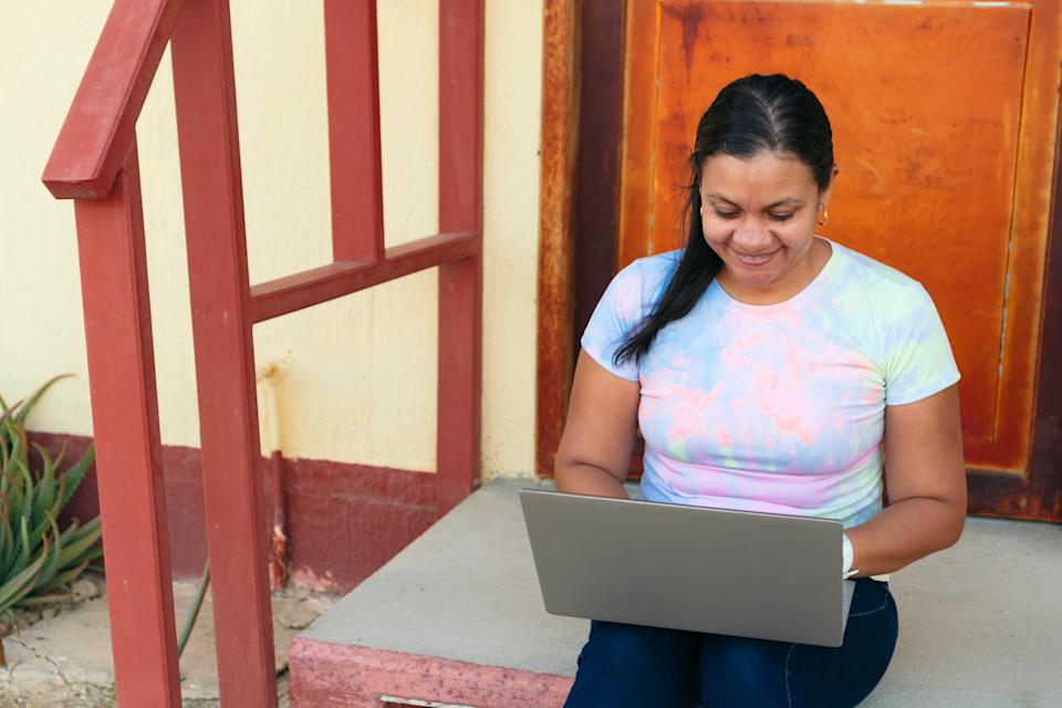 Hispanic woman working with her laptop outside her home