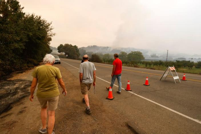 Evacuated residents Esther Brunswick, her husband Ron Brunswick, and Chris Hale walk away from a police checkpoint after trying to check on their homes, in Deer Park, California