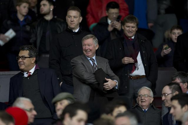 Manchester United's former manager Alex Ferguson, center, takes his seat before the team's English Premier League soccer match against Manchester City at Old Trafford Stadium, Manchester, England, Tuesday March 25, 2014. (AP Photo/Jon Super)