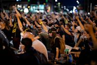Demonstrators raise their fists as they sit in silence for nine minutes in a peaceful protest against the death in Minneapolis police custody of George Floyd, at 19th and Broadway in Denver, Colorado, U.S., June 1, 2020. Picture taken June 1, 2020. REUTERS/Alyson McClaran