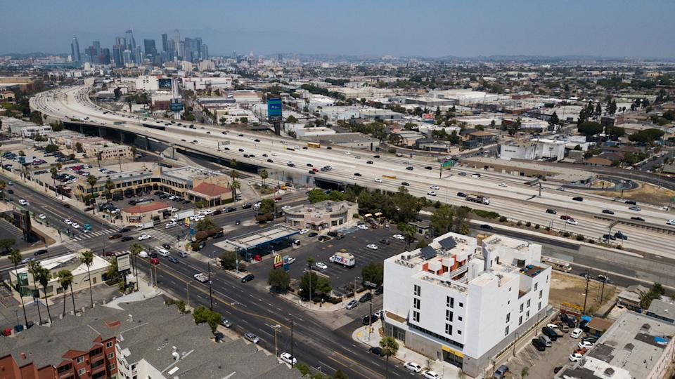 An aerial view of the RISE Apartments, an affordable apartment community for homeless veterans and other people experiencing homelessness stands south of the downtown Los Angeles skyline alongside the 110 freeway on May 12, 2021 in Los Angeles. (Patrick T. Fallon/AFP via Getty Images)
