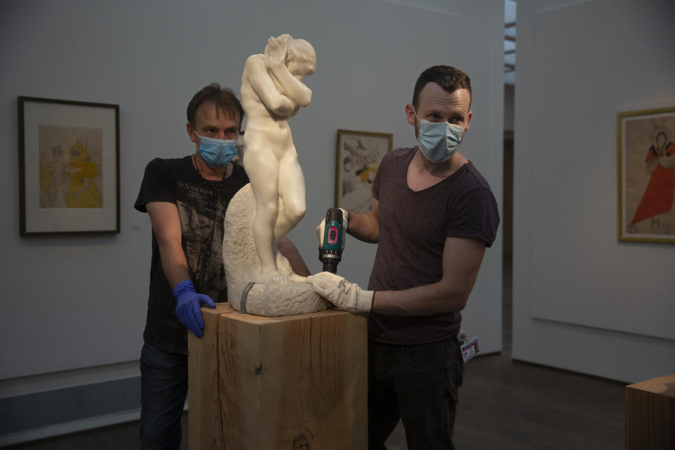 """Workers in the Israel Museum place Auguste Rodin's """"Eve"""" on a pedestal, following five months of closure due to the coronavirus pandemic, in Jerusalem, Tuesday, Aug. 11, 2020. The Israel Museum, the country's largest cultural institution, is returning the priceless Dead Sea scrolls and other treasured artworks to its galleries ahead of this week's reopening to the public. (AP Photo/Maya Alleruzzo)"""