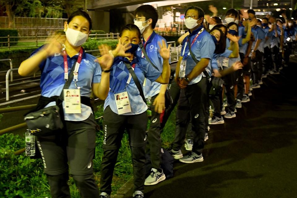 Japanese volunteers wave for visitors as they wait for their bus in front of the the Tokyo Aquatics Centre in Tokyo on July 29, 2021, during the Tokyo 2020 Olympic Games. (Photo by Attila KISBENEDEK / AFP) (Photo by ATTILA KISBENEDEK/AFP via Getty Images)