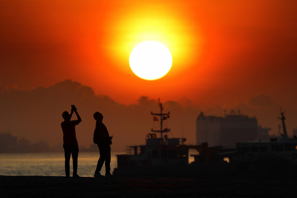 People taking a photo of the sunrise are pictured with vessels anchored along the southern coast on 2 April, 2021 in Singapore. (PHOTO: NurPhoto via Getty Images)
