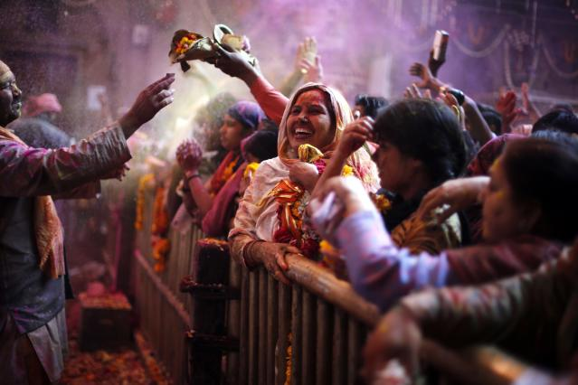 A Hindu woman daubed in coloured powder takes part in Holi celebrations at the Bankey Bihari temple in Vrindavan, in the northern Indian state of Uttar Pradesh, March 13, 2014. Holi, also known as the Festival of Colours, heralds the beginning of spring and is celebrated all over India. REUTERS/Anindito Mukherjee (INDIA - Tags: SOCIETY RELIGION)