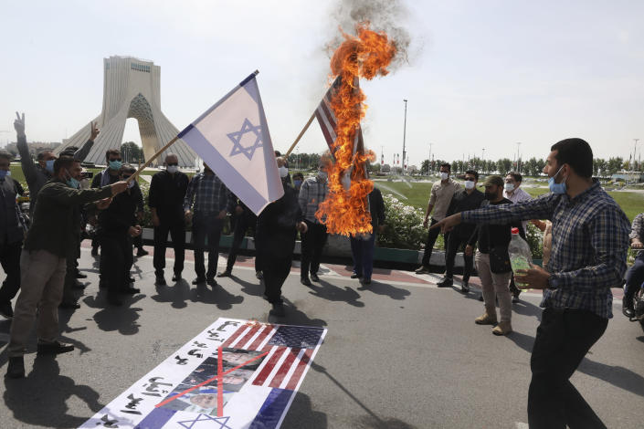 Demonstrators burn representations of Israeli and U.S flags during the annual Al-Quds, or Jerusalem, Day rally, with the Azadi (Freedom) monument tower seen at left, in Tehran, Iran, Friday, May 7, 2021. Iran held a limited anti-Israeli rally amid the coronavirus pandemic to mark the Quds Day. After the late Ayatollah Khomeini, leader of the Islamic Revolution and founder of present-day Iran, toppled the pro-Western Shah in 1979, he declared the last Friday of the Muslim holy month of Ramadan as an international day of struggle against Israel and for the liberation of Jerusalem. (AP Photo/Vahid Salemi)