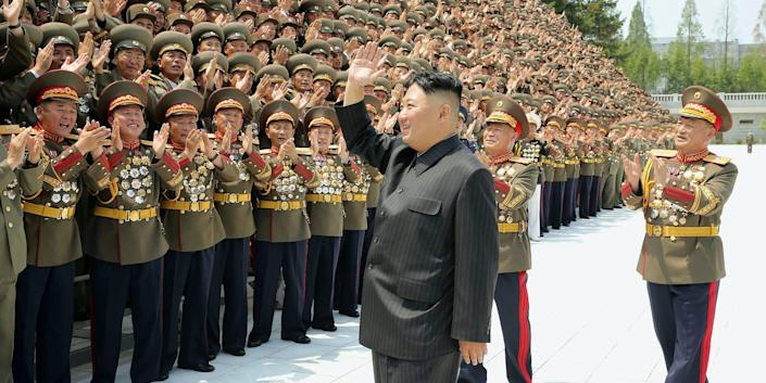 Kim Jong Un waves at a crowd of applausing North Korean soldiers in a black suit, July 2021 in Pyongyang