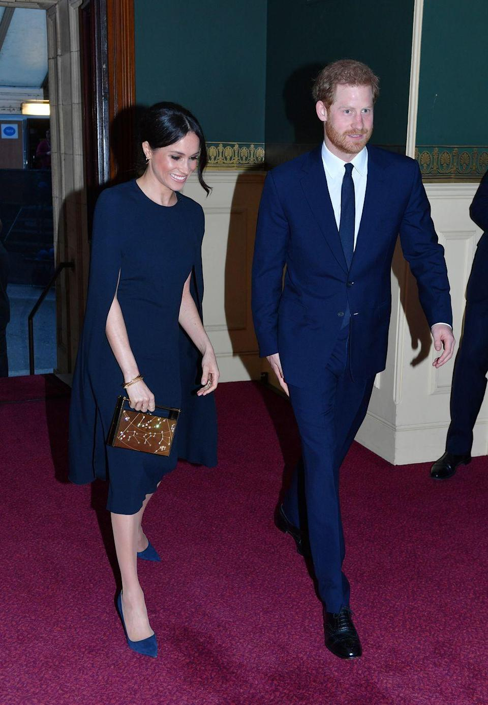 """<p>Markle's sophisticated evening look combined fashion with formality. She paired her navy Stella by Stella McCartney cape dress (longer version available <a class=""""link rapid-noclick-resp"""" href=""""https://www.farfetch.com/uk/shopping/women/stella-mccartney-long-cape-dress-item-12732342.aspx?storeid=9984&size=19&pid=googleadwords_int&af_channel=Search&c=629762120&af_c_id=629762120&af_keywords=aud-169879449902%3Apla-381862307486&af_adset_id=51529112772&af_ad_id=217936171101&is_retargeting=true&gclid=EAIaIQobChMIh7Pqz4fQ2gIVr7vtCh3sbgEsEAQYASABEgI_R_D_BwE"""" rel=""""nofollow noopener"""" target=""""_blank"""" data-ylk=""""slk:here"""">here</a>), with a pair of Manolo Blahnik BB pumps. She carried a chic <a class=""""link rapid-noclick-resp"""" href=""""https://www.modaoperandi.com/naeem-khan-ss17/armory-zodiac-clutch"""" rel=""""nofollow noopener"""" target=""""_blank"""" data-ylk=""""slk:Naeem Khan Armory Zodiac clutch bag"""">Naeem Khan Armory Zodiac clutch bag</a> (sold out but similar zodiac-inspired pieces <a class=""""link rapid-noclick-resp"""" href=""""https://www.elle.com/uk/fashion/what-to-wear/articles/g31277/zodiac-star-sign-horoscope-gifts-jewellery-clothes-accessories/"""" rel=""""nofollow noopener"""" target=""""_blank"""" data-ylk=""""slk:here"""">here</a>) to complete the outfit.</p>"""