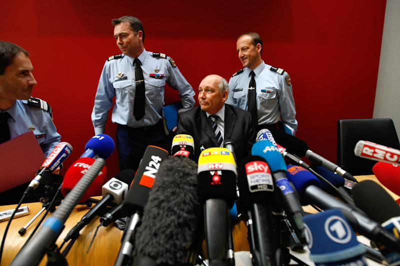 Albertville prosecutor Patrick Quincy, center, arrives with investigators for a press conference in the Albertville law court, French Alps, Wednesday Jan. 8, 2014. Two minutes of footage from a camera on Michael Schumacher's ski helmet showed the Formula One great was clearly skiing off a groomed trail when he lost his balance and crashed, leaving him with critical head injuries, investigators said Wednesday. The investigators said they have ruled out problems with his skis, trail conditions and signage. Although they would not estimate Schumacher's speed, they said it was not considered a significant factor in the Dec. 29 crash at the Meribel resort in the French Alps. (AP Photo/Claude Paris)