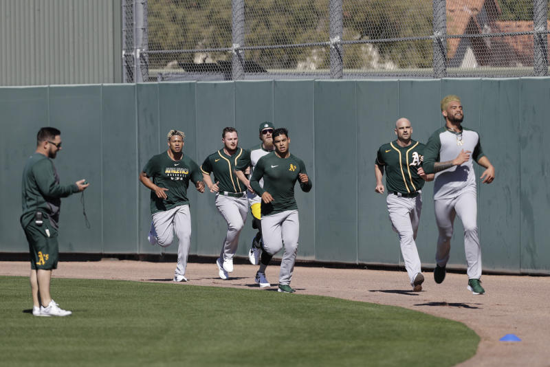 Oakland Athletics' Sean Manaea, front, leads a group of pitchers running during spring training baseball practice, Thursday, Feb. 13, 2020, in Mesa, Ariz. (AP Photo/Darron Cummings)