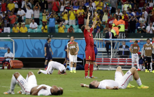 Exhausted US players lie on the ground as Belgium's Axel Witsel (6) celebrates at the end of the extra time during the World Cup round of 16 soccer match between Belgium and the USA at the Arena Fonte Nova in Salvador, Brazil, Tuesday, July 1, 2014. Belgium held on to beat US 2-1 in extra time.(AP Photo/Felipe Dana)
