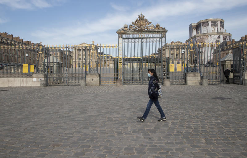 FILE - In this April 21, 2020 file photo, a woman walks past the closed Chateau de Versailles, west of Paris. Iconic sites that are among some of France's biggest tourist draws won't reopen when the country lifts most of its coronavirus restrictions next week. Neither the Louvre Museum, the Eiffel Tower nor the Versailles Palace will be reopening next week when France lifts many of its remaining coronavirus lockdown restrictions. (AP Photo/Michel Euler, File)