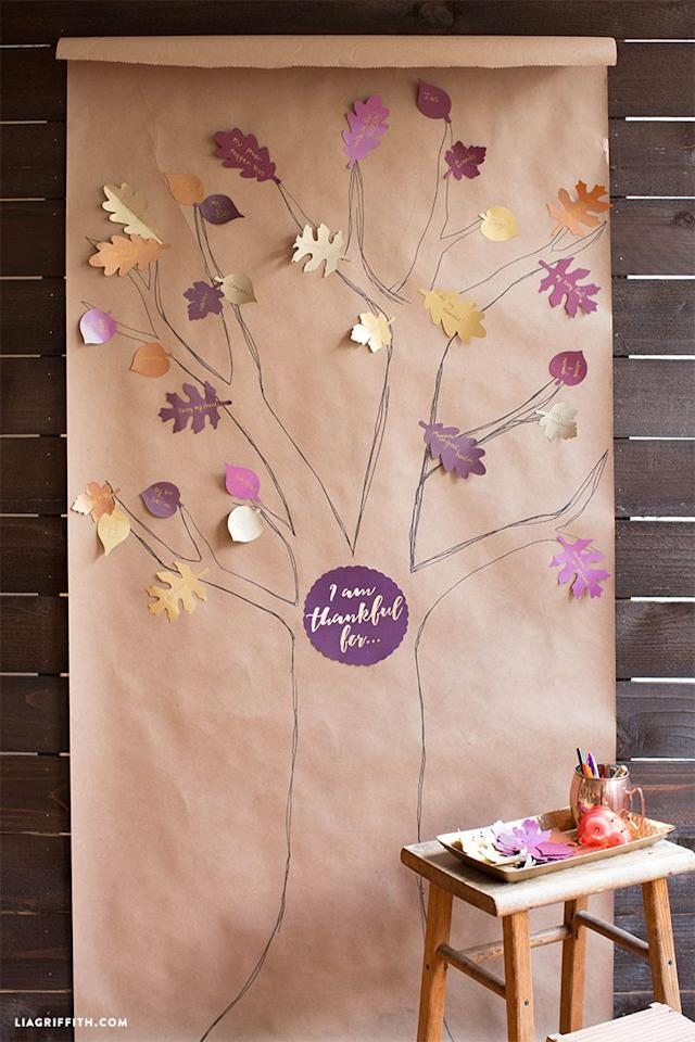 "<p>Skip the centerpiece and DIY some Thanksgiving wall art instead. If you can draw a tree, you can make this.</p><p>Get the tutorial at <a rel=""nofollow"" href=""https://liagriffith.com/thankful-tree-kids-activity/"">Lia Griffith</a>.</p>"