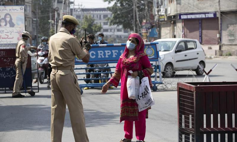 A Kashmiri woman asks a police officer if she can cross the street in Srinagar.