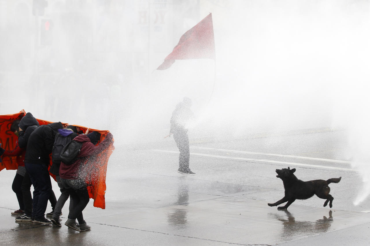 Student protesters are hit by a jet of water as they clash with riot policemen during a demonstration against the government to demand changes in the public state education system in Santiago, August 23, 2012. Chilean students have been protesting against what they say is profiteering in the state education system. REUTERS/Ivan Alvarado (CHILE - Tags: POLITICS CIVIL UNREST EDUCATION TPX IMAGES OF THE DAY)