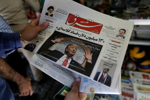 A man holds a newspaper in Tehran