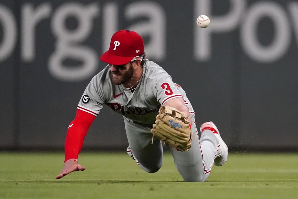 Philadelphia Phillies right fielder Bryce Harper (3) dives for a ball hit for a double by Atlanta Braves' Dansby Swanson in the fifth inning of a baseball game Friday, May 7, 2021, in Atlanta. (AP Photo/John Bazemore)