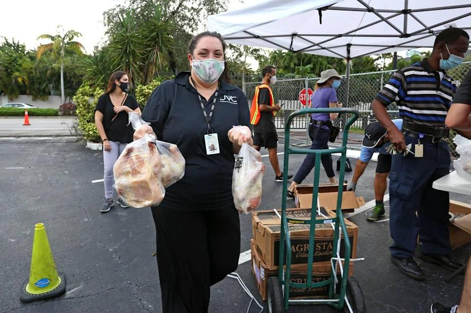 Lori Tabachnikoff, director of the Jewish Volunteer Center, carries frozen chickens during a kosher food distribution event at the Greater Miami Jewish Federation parking lot in response to widespread economic hardship and food insecurity brought on by the COVID-19 pandemic, in Miami, Florida Friday, October 16, 2020.