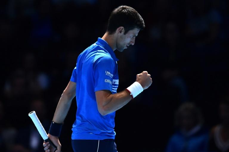 Novak Djokovic celebrates winning the first set against Dominic Thiem during their round-robin match at the ATP Finals