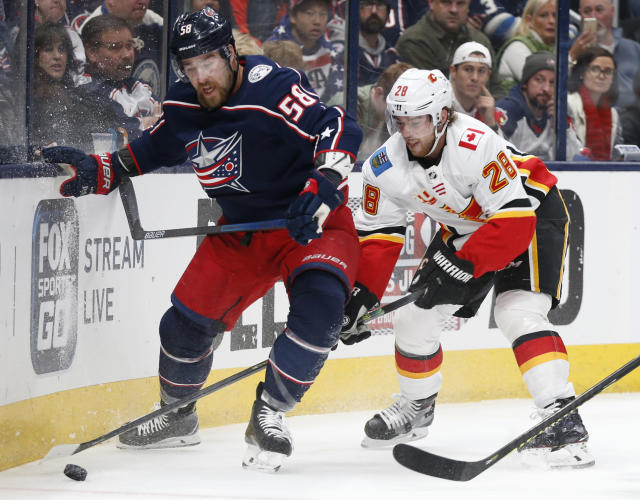Columbus Blue Jackets' David Savard, left, and Calgary Flames' Elias Lindholm, of Sweden, fight for the puck during the first period of an NHL hockey game Saturday, Nov. 2, 2019, in Columbus, Ohio. (AP Photo/Jay LaPrete)