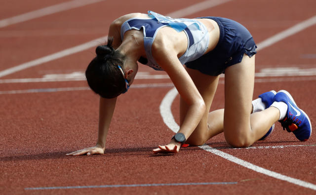 South Korea's Choi Kyungsun rests on the track after completing the women's marathon during the athletics competition at the 18th Asian Games in Jakarta, Indonesia, Sunday, Aug. 26, 2018. (AP Photo/Bernat Armangue)