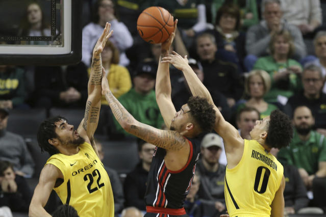 Oregon's Addison Patterson, left, and Will Richardson, right, pressure Utah's Timmy Allen during the first half of an NCAA college basketball game in Eugene, Ore., Sunday, Feb. 16, 2020. (AP Photo/Chris Pietsch)