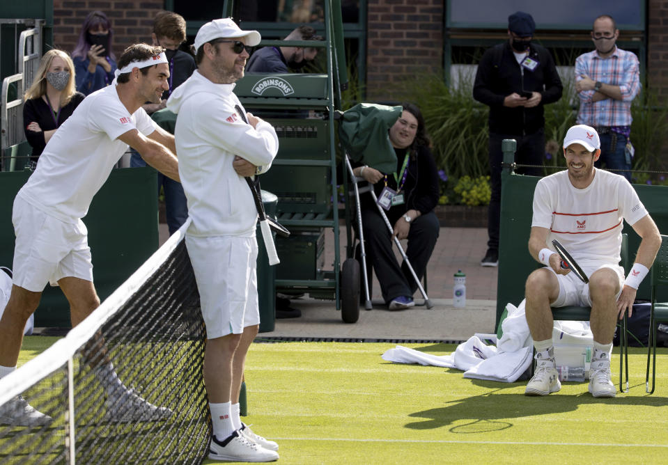 Switzerland's Roger Federer, left, and Britain's Andy Murray, right, on Court 14 for a practice session prior to the Wimbledon Tennis Championships in London, Friday June 25, 2021. (David Gray/Pool via AP)