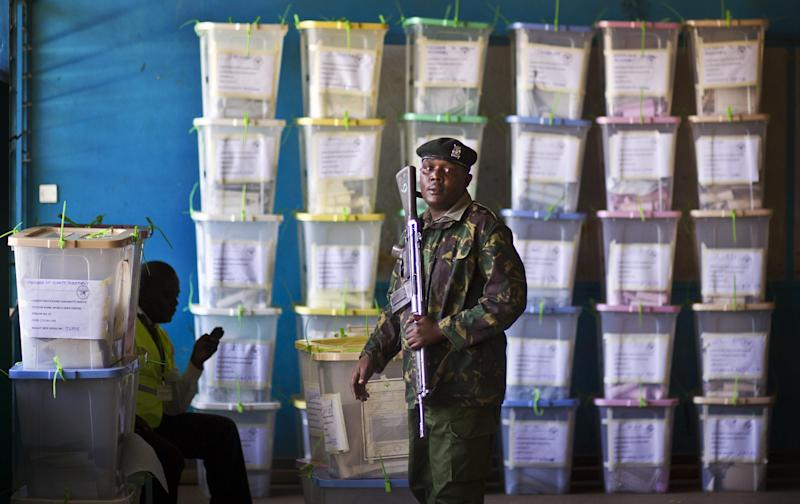 FILE - In this Tuesday, March 5, 2013 file photo, an officer of the prisons service helps to carry ballot boxes for stacking after their results were tallied, at a vote tallying center in Nairobi, Kenya. Vote totals for Kenya's president-elect mysteriously increased between the time the ballot numbers were announced at some remote polling centers and when they reached the national tallying center in the capital, a lawyer for a civil society group told the country's Supreme Court on Wednesday, March 27, 2013. (AP Photo/Ben Curtis, File)
