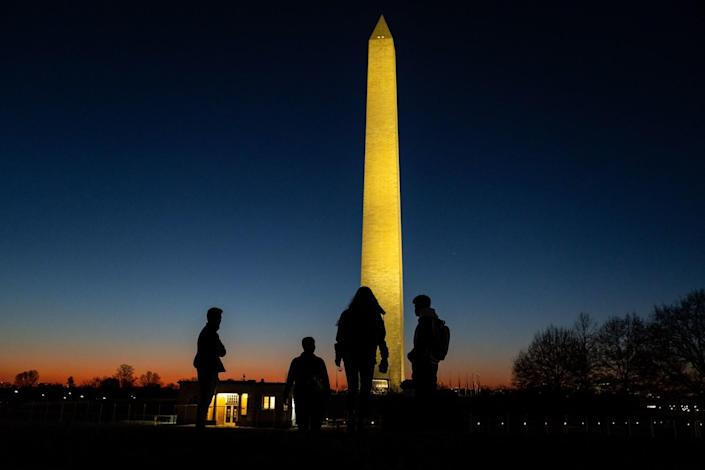 People walk on the National Mall with the Washington Monument illuminated in the evening sky.