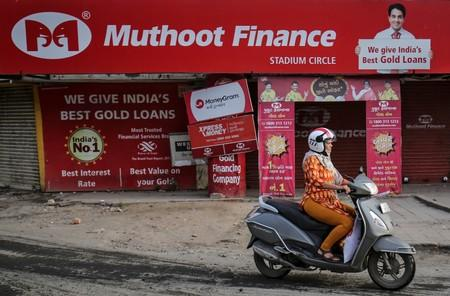A woman rides her scooter past a Muthoot Finance branch in Ahmedabad