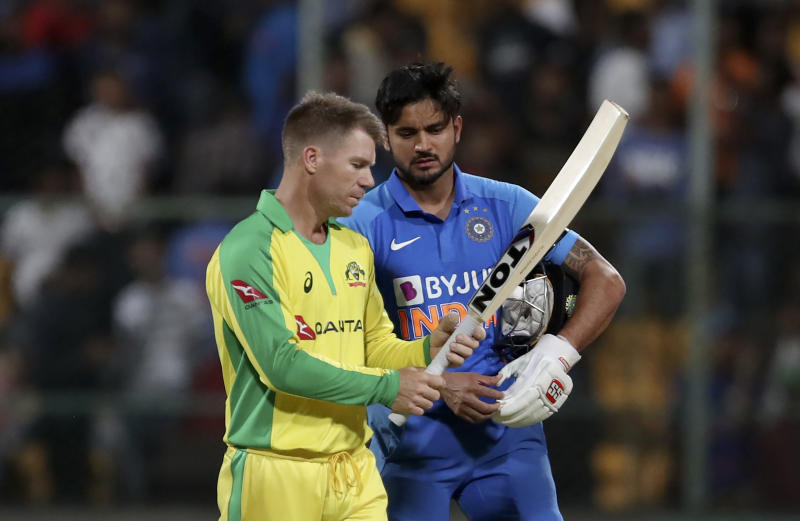 Australia's David Warner, left, checks out the bat of India's Manish Pandey after India won the third one-day international cricket match between India and Australia in Bangalore, India, Sunday, Jan. 19, 2020. (AP Photo/Aijaz Rahi)