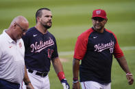 Washington Nationals' Kyle Schwarber, center, hobbles off the field next to trainer Paul Lessard, left, and manager Dave Martinez during the second inning of a baseball game against the Los Angeles Dodgers, Friday, July 2, 2021, in Washington. (AP Photo/Julio Cortez)