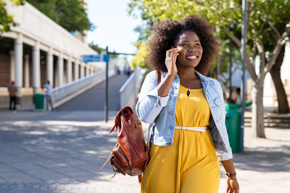 Happy young woman in casual walking while talking over phone. Cheerfuln girl with curly hair using smartphone.