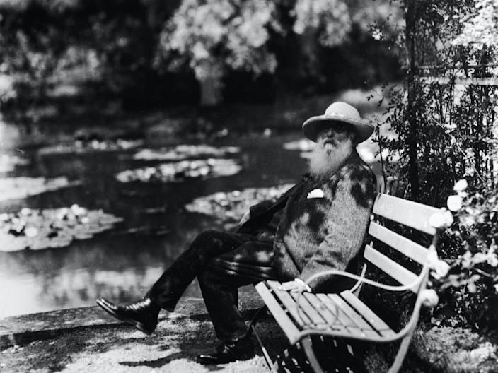 French impressionist painter Claude Monet (1840 - 1926) sits on a bench beside the water lily pond in his home garden, Giverny, France, 1910s.