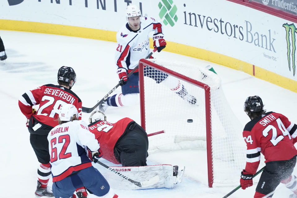 Washington Capitals right wing Garnet Hathaway (21) scores a goal past New Jersey Devils goaltender Mackenzie Blackwood (29) during the first period of an NHL hockey game, Saturday, Feb. 27, 2021, in Newark, N.J. (AP Photo/Mary Altaffer)