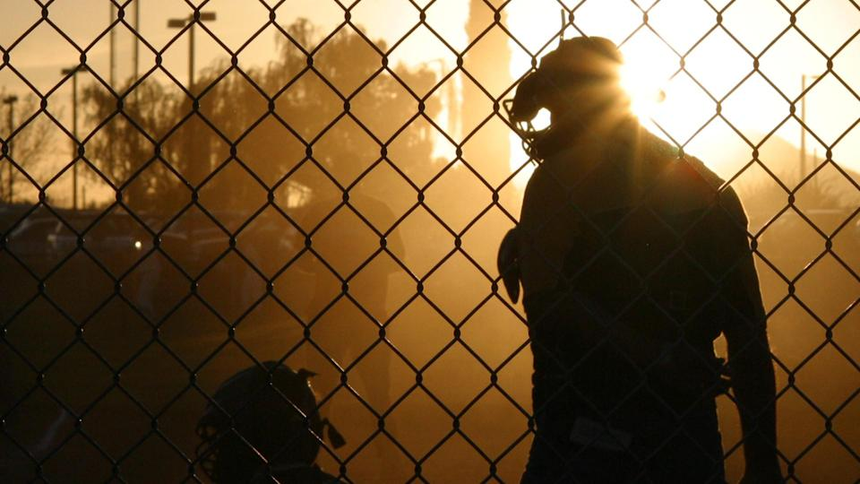 A sunset silhouetted umpire talking to a little league catcher.