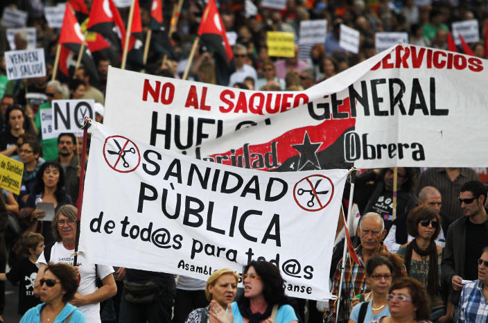 """Protestors hold a banner reading """"public healthcare for everyone"""" and """"general strike"""" as they march against healthcare austerity measures announced by the Spanish government and to defend the public healthcare system in Madrid, Spain, Saturday, Oct. 6, 2012. Hundreds of Spaniards concerned with government cuts to healthcare and civil servants hit with another freeze on their wages for next year held a protest in downtown Madrid. (AP Photo/Andres Kudacki)"""