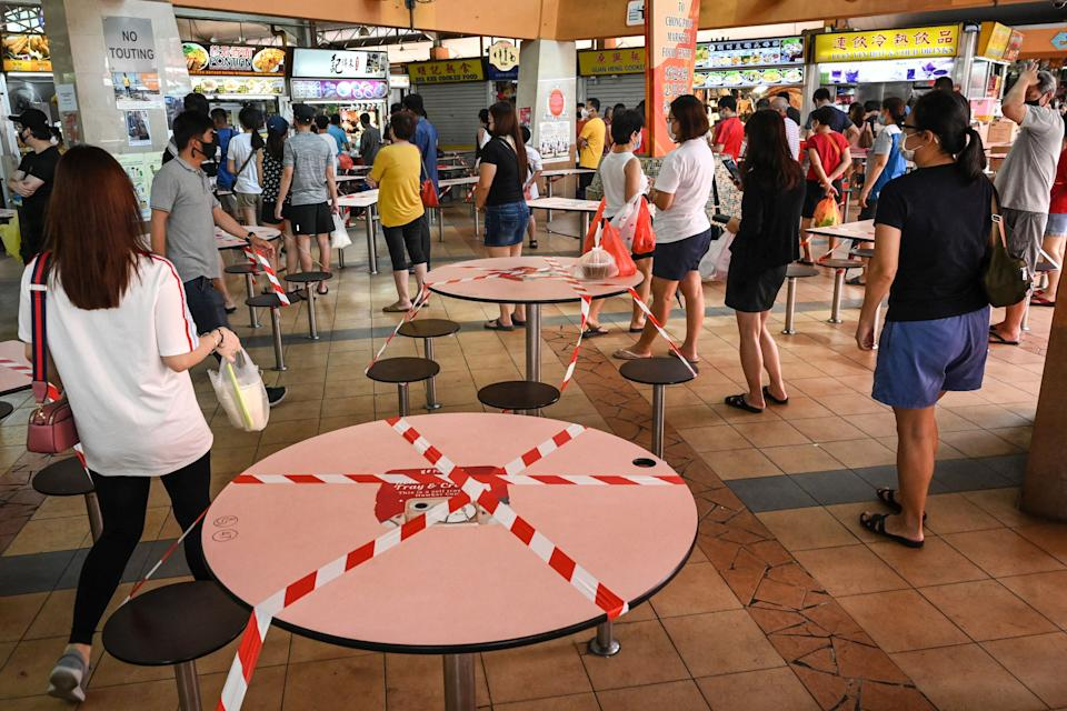 People queue to buy food as takeaway orders, as tables and chairs are cordoned off to prevent people from dining at a hawker centre in Singapore on Sunday (16 May). (PHOTO: Getty Images)