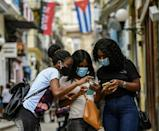 Three women in Havana check their mobile phones after internet access was restored in Cuba